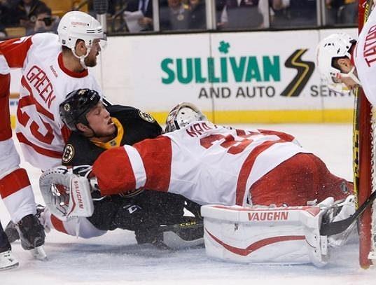 Český brankář Petr Mrázek (34) z Detroitu Red Wings v souboji s jedním z útočníků Bostonu Bruins.