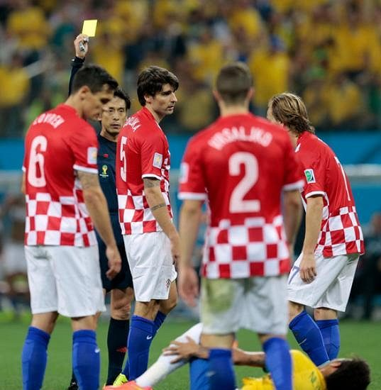 Sudí Juiči Nišimura dává chorvatskému obránci Vedranu Čorlukovi (uprostřed) žlutou kartu.