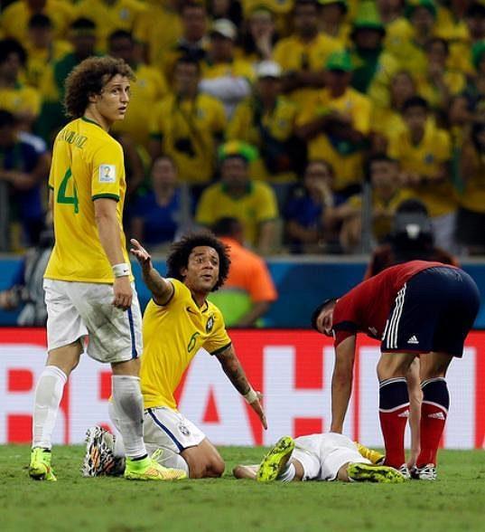 Brazilec Marcelo volá sudího a pomoc ke zraněnému Neymarovi. Vlevo David Luiz.