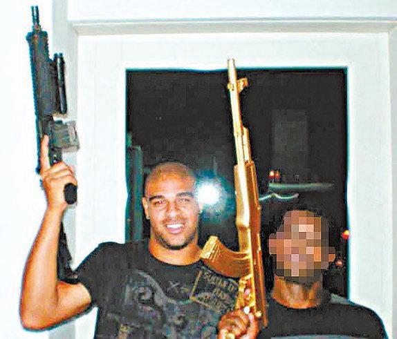Adriano s automatickou zbraní.