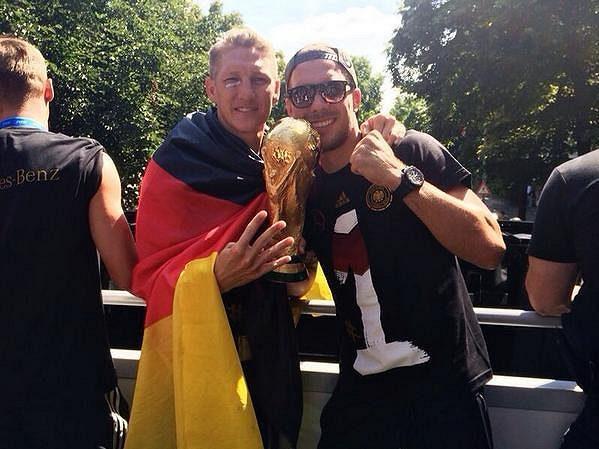 Bastian Schweinsteiger (vlevo) a Lukas Podolski slaví v berlínských ulicích.