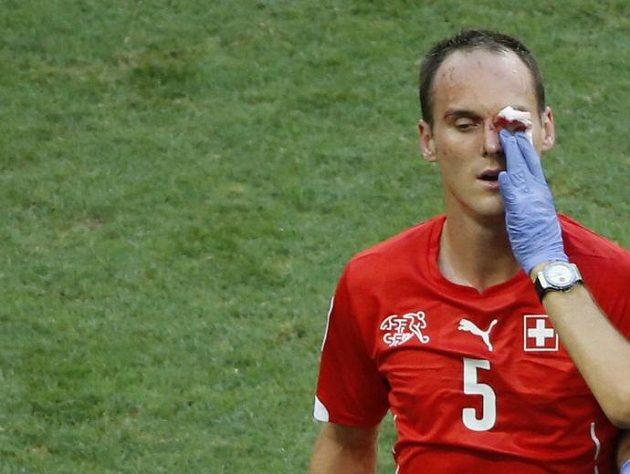 Švýcarský obránce Steve von Bergen je ošetřován v duelu s Francií.