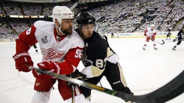 Kapitán Pittsburghu Sidney Crosby v souboji s Tomasem Holmströmem z Detroitu