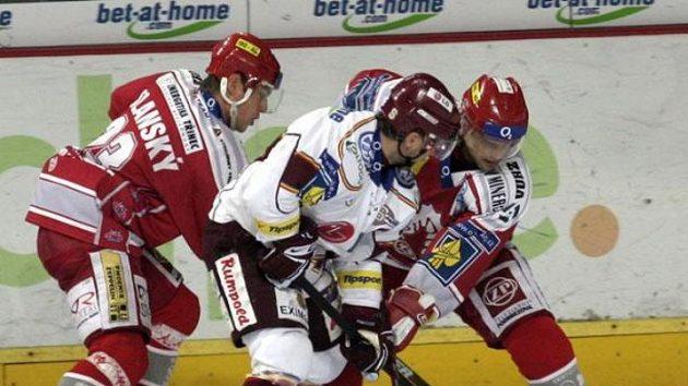 Hokejista Třince Jiří Polanský odváží puk během utkání na Spartě.