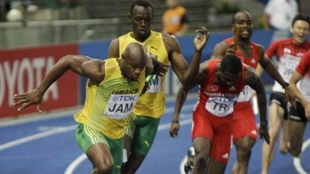 Jamajčan Asafa Powell (vlevo) přebírá štafetu od Usaina Bolta.