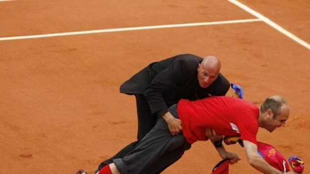 """Člen ochranky """"skládá"""" na antuku vetřelce při finále French Open."""