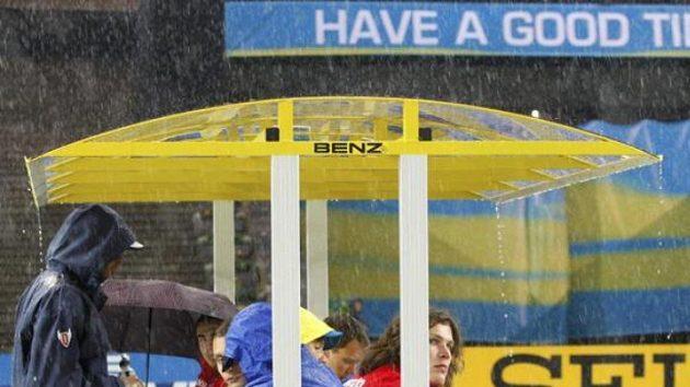 Atleti se schovávají před prudkým deštěm na Olympijském stadiónu v Berlíně.