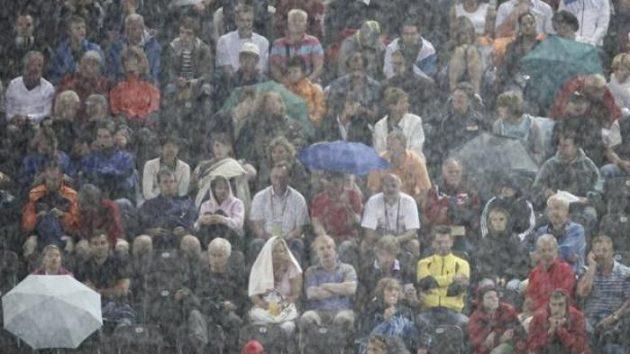 Diváci atletického MS skrytí za clonou prudkého deště na Olympijském stadiónu v Berlíně.