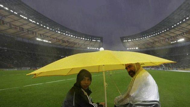 Technický personál atletického MS se ukrývá před prudkým deštěm na Olympijském stadiónu.