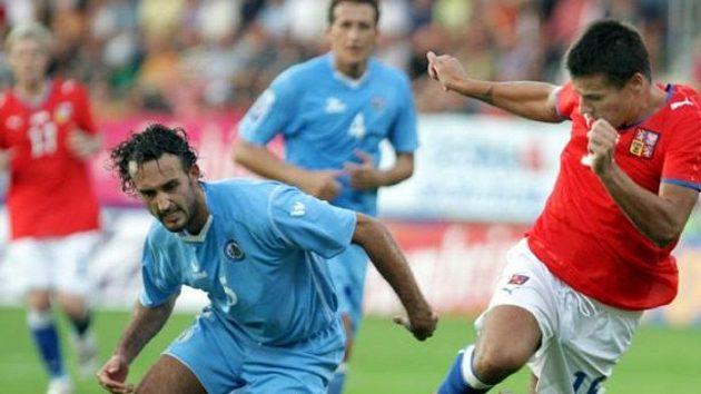 Fotbalista Milan Baroš proniká kolem Della Valleho ze San Marina