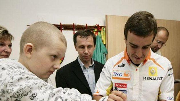 Fernando Alonso se podepisuje malému pacientovi onkologického oddělení v Motole.