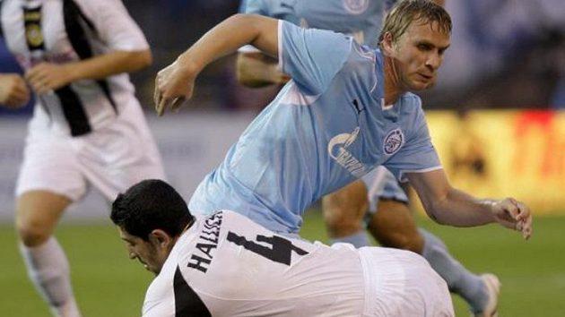 Fotbalista Rafik Halliche z týmu nacional Madeira bojuje o míč se Sergejem Kornilenkem (uprostřed) ze Zenitu Petrohrad v play-off Evropské ligy.