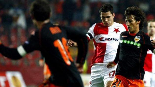 Marek Suchý (uprostřed) ze Slavie se snaží obrat o míč Davida Silvu z Valencie.