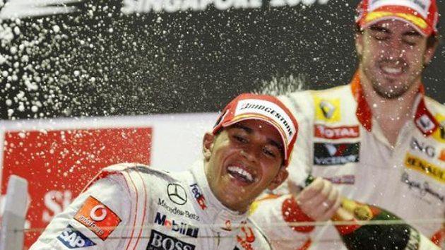 Lewis Hamilton slaví triumf ve Velké ceně Singapuru. Vzadu Fernando Alonso, který skončil třetí.