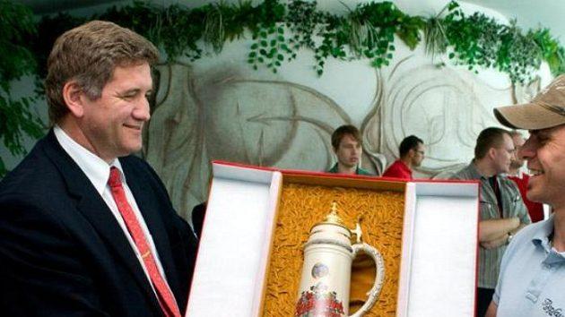 Generální ředitel Budějovického Budvaru Jiří Boček předává dar kapitánu hokejové reprezentace Tomáši Rolinkovi.