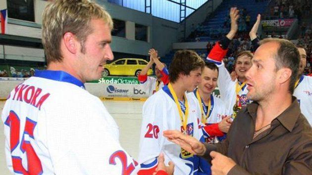 Kapitán extraligové Plzně Martin Straka (vpravo) předává zlaté madaile pro mistry světa českým hokejbalistům.