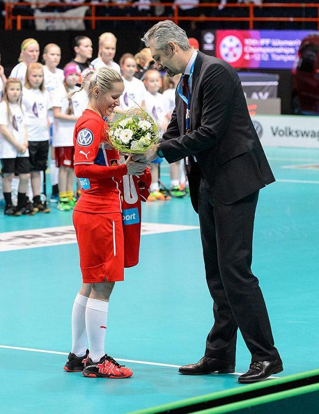 Florbalistka Denisa Billá přebírá od prezidenta Českého florbalu Filipa Šumana kytici a památeční dres připomínající její 100. zápas v národním týmu na MS ve Finsku.