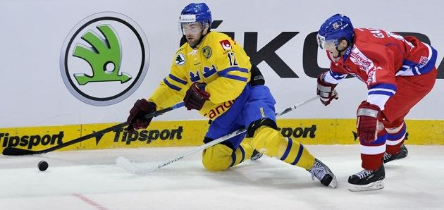 Obránce české hokejové reprezentace Lukáš Galvas (vpravo) se snaží zastavit Fredrika Petterssona ze Švédska.