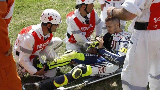 Zdravotníci nakládají zraněného Rossiho na nosítka.