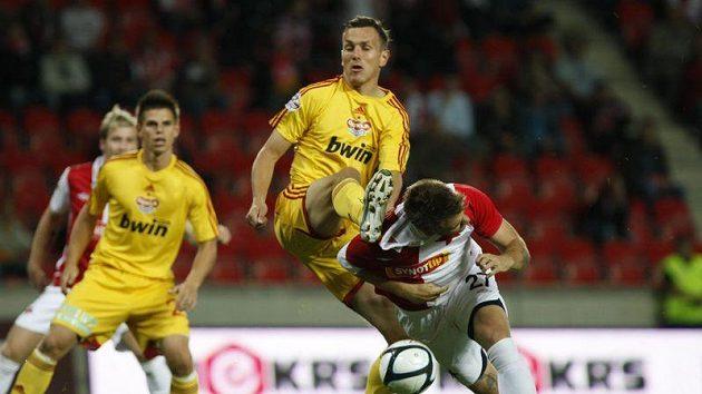 Ondřej Švejdík z Dukly odehrává míč před slávistou Zbyňkem Pospěchem.