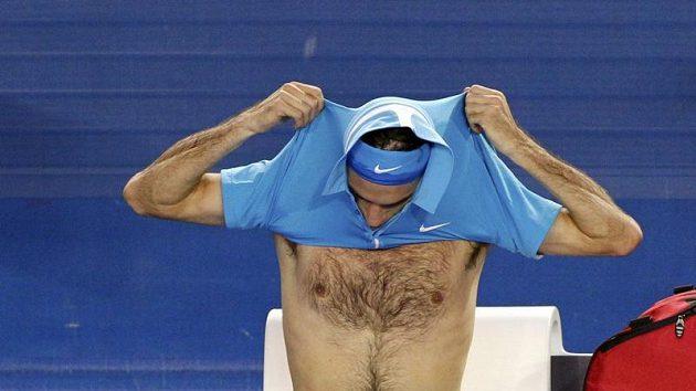 Roger Federer se převléká mezi výměnami