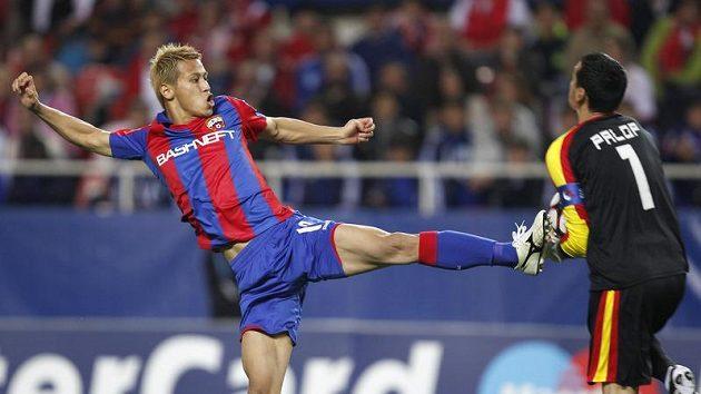 Keisuke Honda z CSKA Moskva (vlevo) bojuje nevybíravým způsobem o míč s gólmanem Sevilly Andresem Palopem v odvetě osmifinále Ligy mistrů.