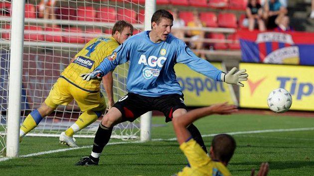 Brankář Teplic Tomáš Grigar (uprostřed) kontroluje míč, který prolétá jeho pokutovým územím.