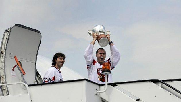 Český kapitán Tomáš Rolinek se raduje s pohárem, za ním vychází z letadla Jaromír Jágr.