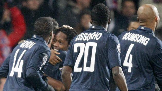 Fotbalisté Lyonu objímají střelce gólu Jeana Makouna.
