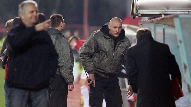 František Straka (vpravo) pod dohledem bodyguardů během zápasu na Žižkově