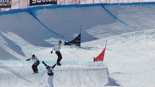 Michal Novotný (vlevo, žlutý dres) vede krátce před cílem svého osmifinále při Světovém poháru snowboardcrossařů ve švýcarské Arose.