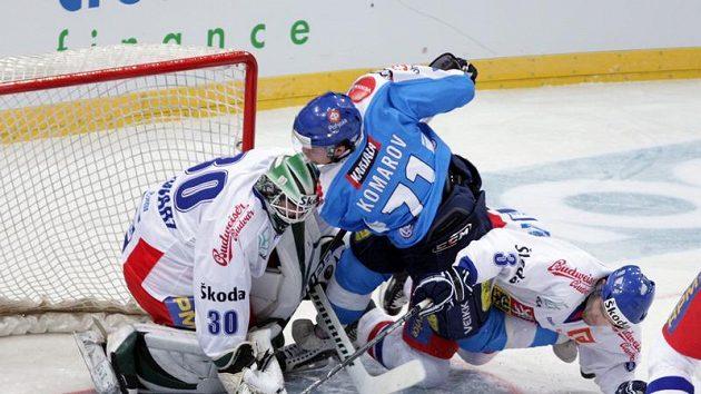 Brankář Marek Schwarz stojí v brankovišti, před kterým svádějí souboj Fin Komarov a Vladimír Sičák.