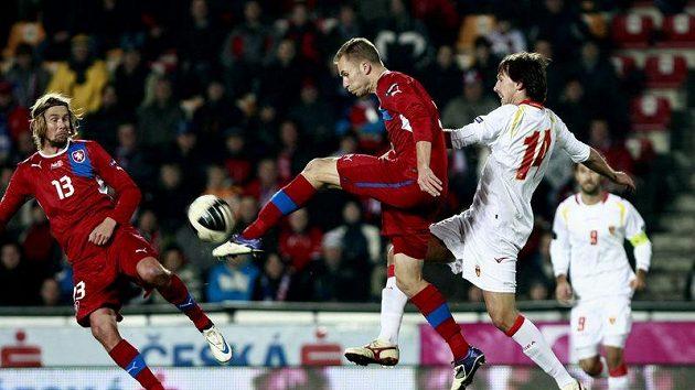 Michal Kadlec (uprostřed) odkopává míč před dotírajícím Dejanem Demjanovičem z Černé Hory.