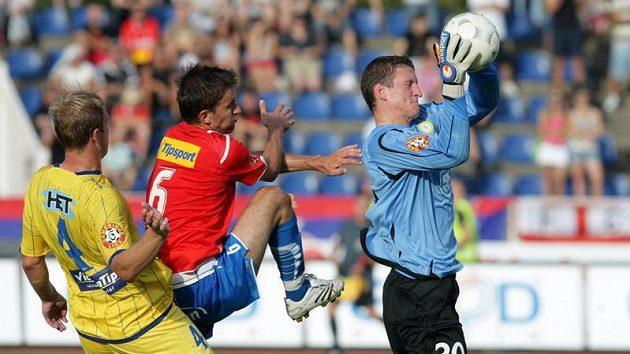 Brankář Teplic Tomáš Grigar (vpravo) chytá míč před dotírajícím plzeňským útočníkem Markem Bakošem (uprostřed), jehož brání Martin Klein.
