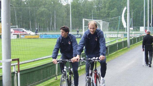 Roman Hubník (vpravo) a Kamil Vacek odjíždějí na kolech z tréninku Sparty během přípravy ve Františkových Lázních.