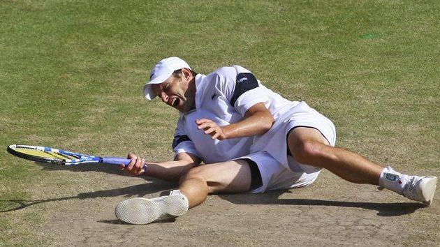 Americký tenista Andy Roddick leží na zemi po jednom z úderů během finále Wimbledonu proti Rogeru Federerovi ze Švýcarska.