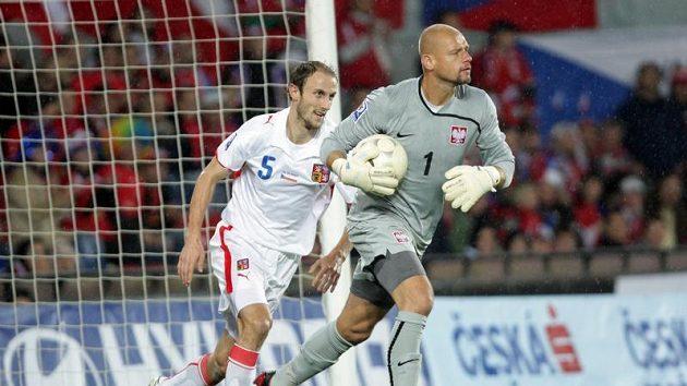 Gólman Polska Kowalewski utíká s míčem v ruce před Romanem Hubníkem