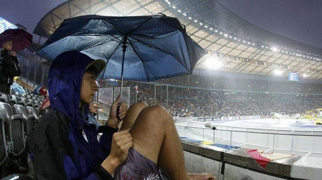 Diváci atletického MS se schovávají před deštěm na Olympijském stadiónu v Berlíně.