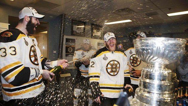 Zdeno Chára (vlevo) stříká šampaňské na spoluhráče z Bostonu po vítězství ve Stanleyově poháru
