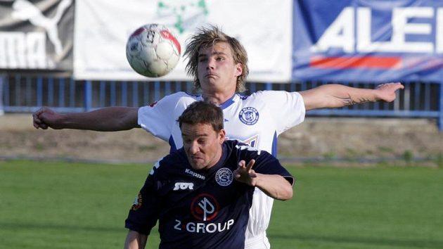 Kladenský Vít Beneš skáče po míči za Petrem Švancarou ze Slovácka