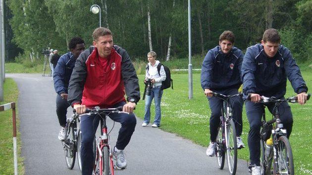 Trenér Martin Hašek (vlevo) a hráči Sparty odjíždějí z tréninku během přípravy ve Františkových Lázních.
