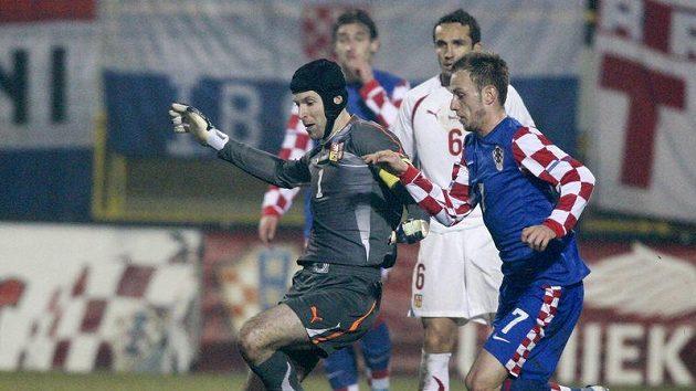 Situace předcházející čtvrtému gólu Chorvatska. Brankář Petr Čech (vlevo) se snaží odklidit míč před Ivanem Rakitičem.