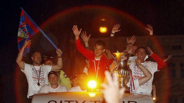 Fotbalisté Plzně se na střeše autobusu radují ze zisku poháru pro vítěze ligy.
