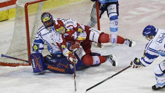Důrazný třinecký forvard Martin Růžička (v červeném) atakuje kladenského gólmana Lukáše Cikánka.