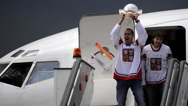 Hokejisté Tomáš Rolinek (s pohárem) a Jaromír Jágr vycházejí z letadla po přistání v Praze.