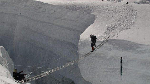 Šerpové přecházejí jednu z trhlin v ledopádu Khumbu.