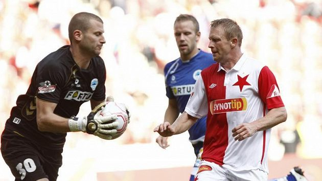 Brankář Liberce David Bičík chytá míč před slávistou Stanislavem Vlčkem.