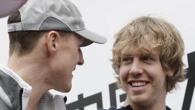 Michael Schumacher při rozhovoru se svým krajanem Sebastianem Vettelem (vpravo), který je pasován do role jeho následníka.