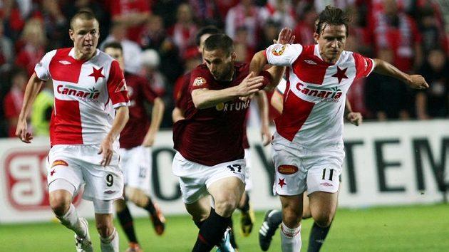 Fotbalisté Slavie Adam Hloušek (vlevo) a Vladimír Šmicer (vpravo) v souboji o míč se sparťanem Janem Holendou v pražském derby
