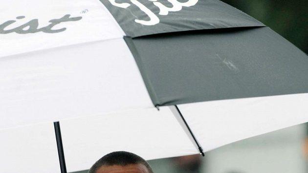 Desetibojař Roman Šebrle se skrývá pod deštníkem během atletického mítinku v Kladně.